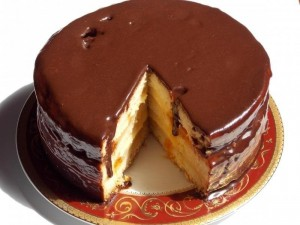 Russian charodeika sponge layers cake with anglaise cream and chocolate coating